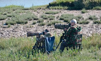 Two men wearing camouflage photographing nature