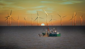 Offshore wind turbines on the horizon with a fishing trawler in the foreground